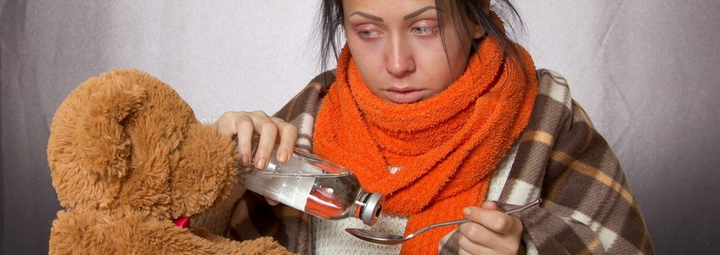 Woman wearing an orange scarf looking cold and taking some medicine